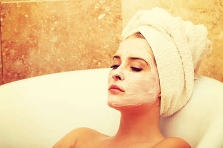 Photo pour Relaxing woman with closed eyes and cream lotion on face - image libre de droit