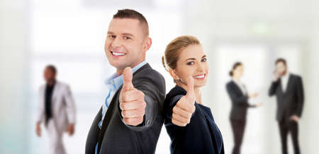 Foto de Happy business couple showing thumbs up. - Imagen libre de derechos