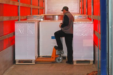 Photo pour Loading goods in lorry truck with pallet jack - image libre de droit