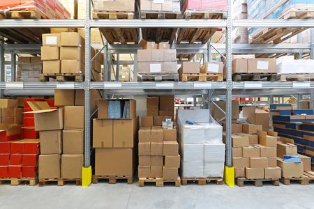 Photo pour Boxes with goods at shelves in warehouse - image libre de droit