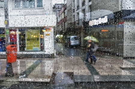 Street scene seen from a parked car during a rain shower.