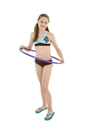 Preteen caucasian girl standing on a white background in a swimsuit holding ahula hoop