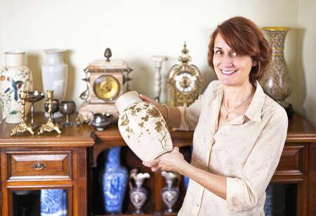 Foto de Proud woman holding vase from her collection of antiques - Imagen libre de derechos
