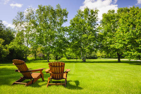 Foto de Two wooden adirondack chairs on lush green lawn with trees - Imagen libre de derechos