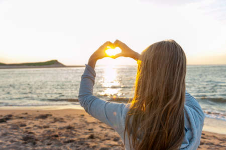 Foto de Blonde young girl holding hands in heart shape framing setting sun at sunset on ocean beach - Imagen libre de derechos