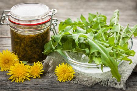 Foto de Foraged edible dandelions flowers and greens with jar of dandelion preserve - Imagen libre de derechos
