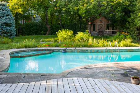 Backyard with outdoor inground residential swimming pool, garden, deck and stone patio