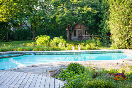 Photo pour Backyard with garden, shed,  outdoor inground residential swimming pool, curved wooden deck and stone patio - image libre de droit