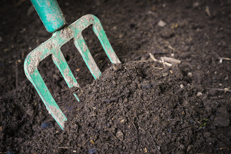 Photo for Garden fork turning  black composted soil in compost bin ready for gardening, close up. - Royalty Free Image