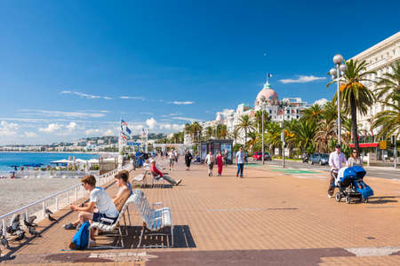 Photo for NICE, FRANCE - OCTOBER 2, 2014: People enjoying sunny weather and view of Mediterranean sea at English promenade (Promenade des Anglais), a great place for walking, jogging, biking or simply relaxing. - Royalty Free Image