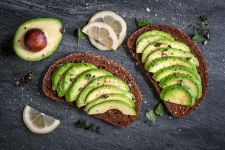 Photo for Avocado sandwich on dark rye bread made with fresh sliced avocados from above - Royalty Free Image