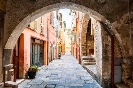 Photo pour Narrow cobblestone street with colorful buildings viewed though stone arch in medieval town Villefranche-sur-Mer on French Riviera, France. - image libre de droit