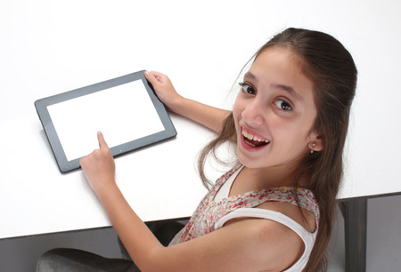 Photo pour Beaitiful preteen girl using a tablet computer. High angle. Clipping path for the screen - image libre de droit