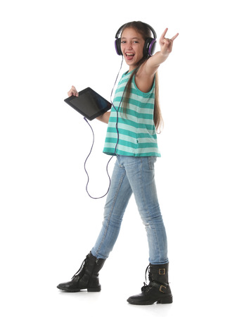 Photo pour Beautiful preteen girl dancing and going crazy using a tablet computer and headphones - image libre de droit