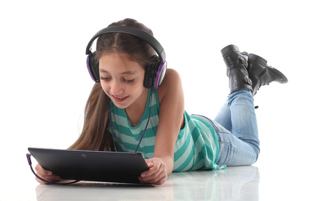 Photo pour Beautiful preteen girl on the floor usin a tablet computer and headphones white background - image libre de droit