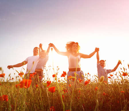 Foto de Happy family playing on the poppy meadow - Imagen libre de derechos