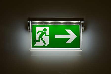 Foto de Emergency exit sign glowing in the dark - Imagen libre de derechos