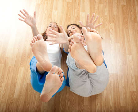 Two beautiful young women having fun and moving the Hands and Feet