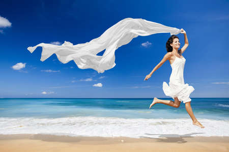 Photo for Beautiful woman running and jumping on the beach with a white scarf - Royalty Free Image