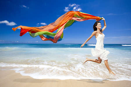 Photo pour Beautiful woman running and jumping in the beach with a colored tisue - image libre de droit