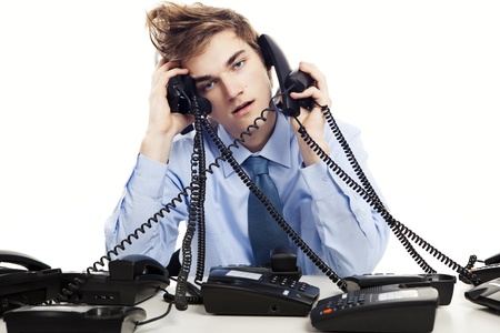 Photo pour Young man sitting in the office and answering several phones at the same time - image libre de droit