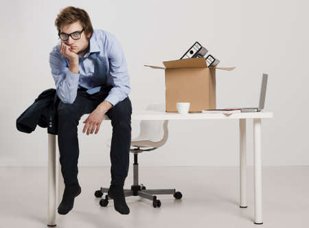 Photo for Young man sitting on the desk after being fired - Royalty Free Image