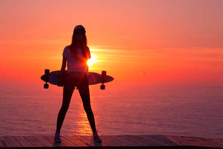 Photo pour Beautiful and fashion young woman posing at teh sunset with a skateboard - image libre de droit