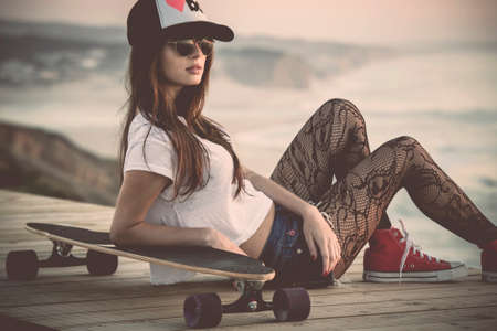 Foto für Beautiful and fashion young woman posing with a skateboard - Lizenzfreies Bild