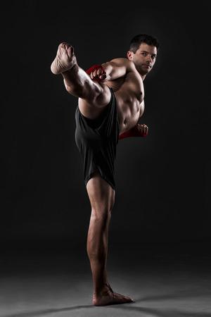 Foto de Portrait of a muscular man practicing body combat against a dark background - Imagen libre de derechos