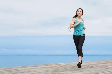 Photo pour Beautiful young woman jogging on a boardwalk and listen music - image libre de droit