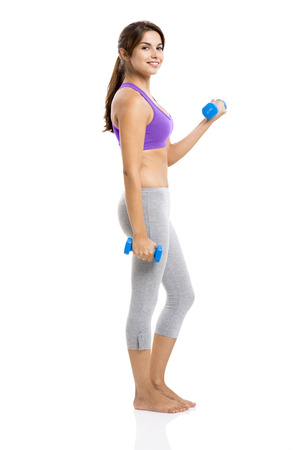 Beautiful and healthy woman lifting weights, isolated over a white background