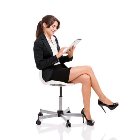 Photo for Happy business woman sitting on chair working with a tablet, isolated over white background - Royalty Free Image