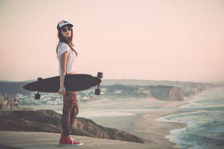 Foto de Beautiful fashion skater girl posing with  a skate board - Imagen libre de derechos
