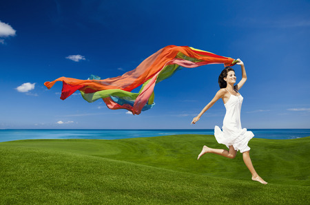 Photo pour Beautiful woman jumping on a green meadow with colored tissues - image libre de droit