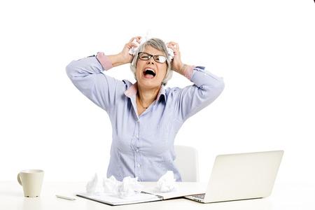 Foto für Stressed elderly woman working in the office with a laptop - Lizenzfreies Bild