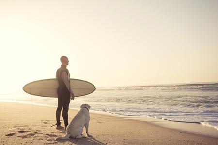 Foto de Surfist on the beach with his best friend - Imagen libre de derechos