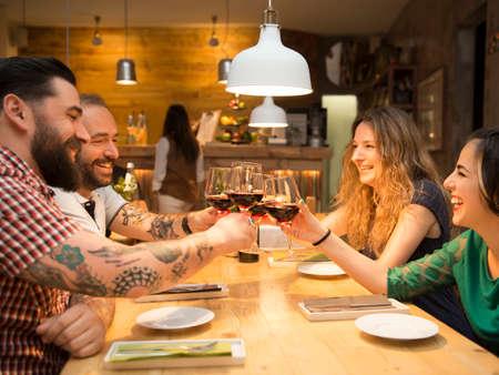 Foto de Group of friends toasting and having a good time at the restaurant - Imagen libre de derechos