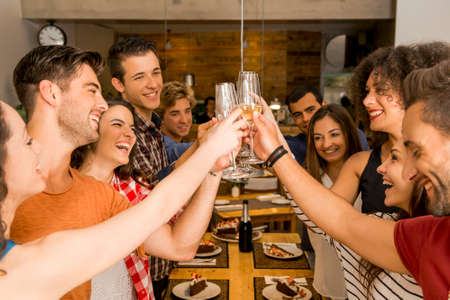 Photo for Group of friends toasting and looking happy at a restaurant - Royalty Free Image
