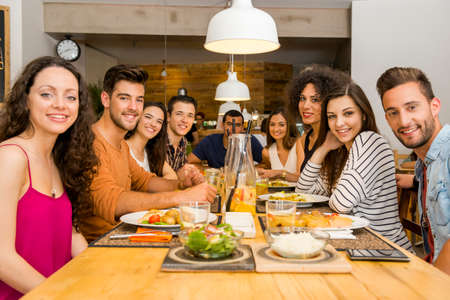 Photo pour Multi-Ethnic Group of happy friends lunching and having fun at the restaurant - image libre de droit