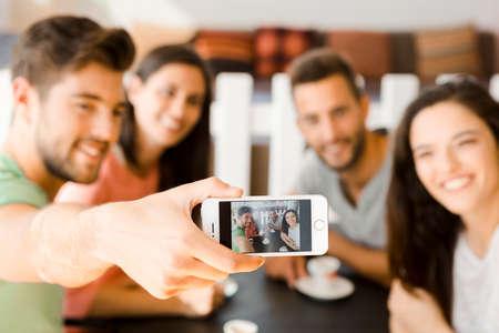 Foto de Group of friends at the coffee shop making a selfie together - Imagen libre de derechos