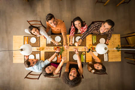 Photo pour Group of people toasting and looking happy at a restaurant - image libre de droit