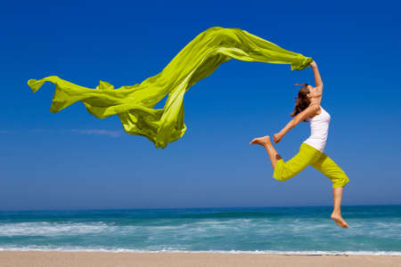 Foto per Beautiful young woman jumping on  the beach with a colored tissue - Immagine Royalty Free