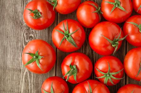 Photo pour Close-up of fresh, ripe tomatoes on wood background - image libre de droit