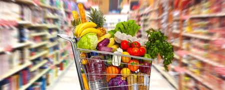 Full shopping grocery cart in supermarket.