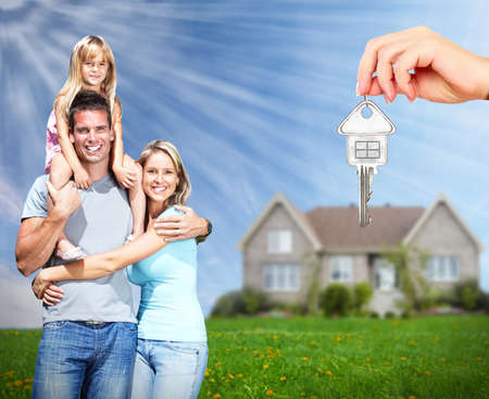 Foto de Happy family near new home. Real estate background. - Imagen libre de derechos