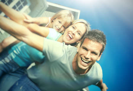 Photo pour Happy smiling family with child over  house background - image libre de droit