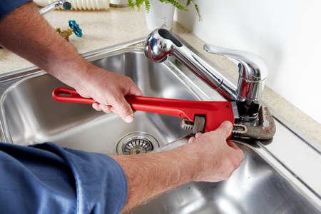 Foto de Hands of professional Plumber with a water tap and wrench. - Imagen libre de derechos