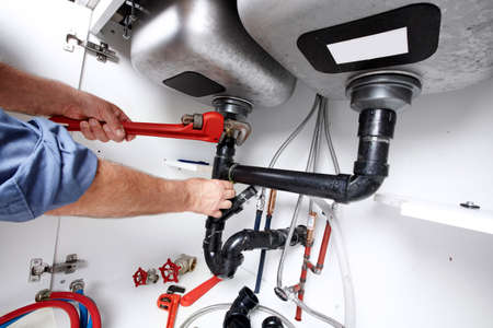 Foto de Hands of professional Plumber with a wrench. Clogged sink. - Imagen libre de derechos