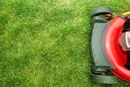 Photo pour Red Lawn mower cutting grass. Gardening concept background - image libre de droit