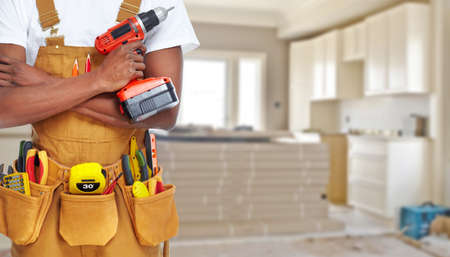 Foto de Builder handyman with construction tools. House renovation background. - Imagen libre de derechos